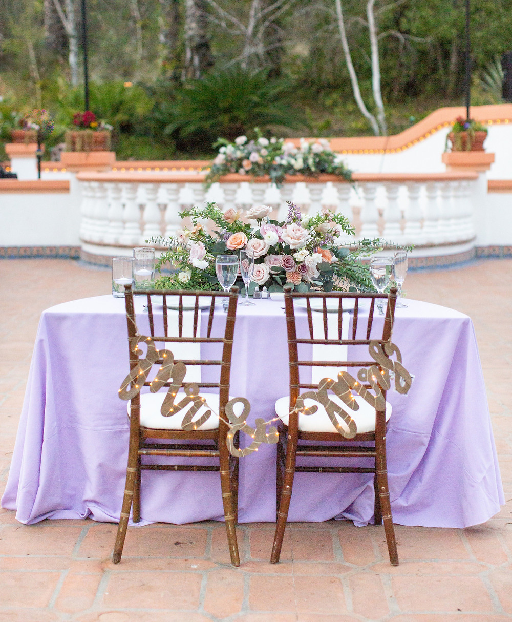 Beautiful Sweetheart Table flowers for a purple wedding, filled with eucalyptus, sweet peas, carnations, ranunculus, lilac, spray roses, and amnesia roses that perfectly matched their purple and mauve color palette  for a stunning wedding at Rancho Las Lomas in Orange County, CA made by San Diego wedding florist Le Champange Projects