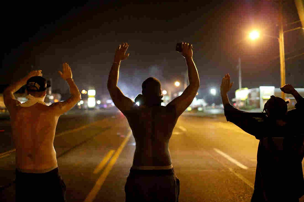 Three men in the middle of the street with hands raised for police officers.