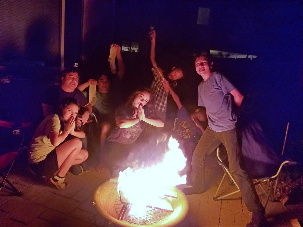 Photo of family gathered around a firepit.