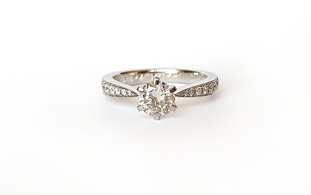 Elegants baltā zelta gredzens, kuram stīpiņa sašaurinās, ietverot centrālo briljantu.