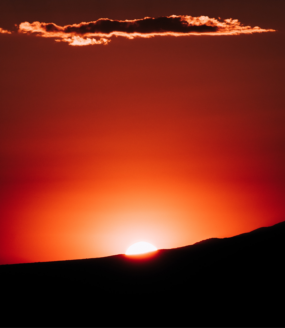 sun behind horizon cloud lit by orange glow
