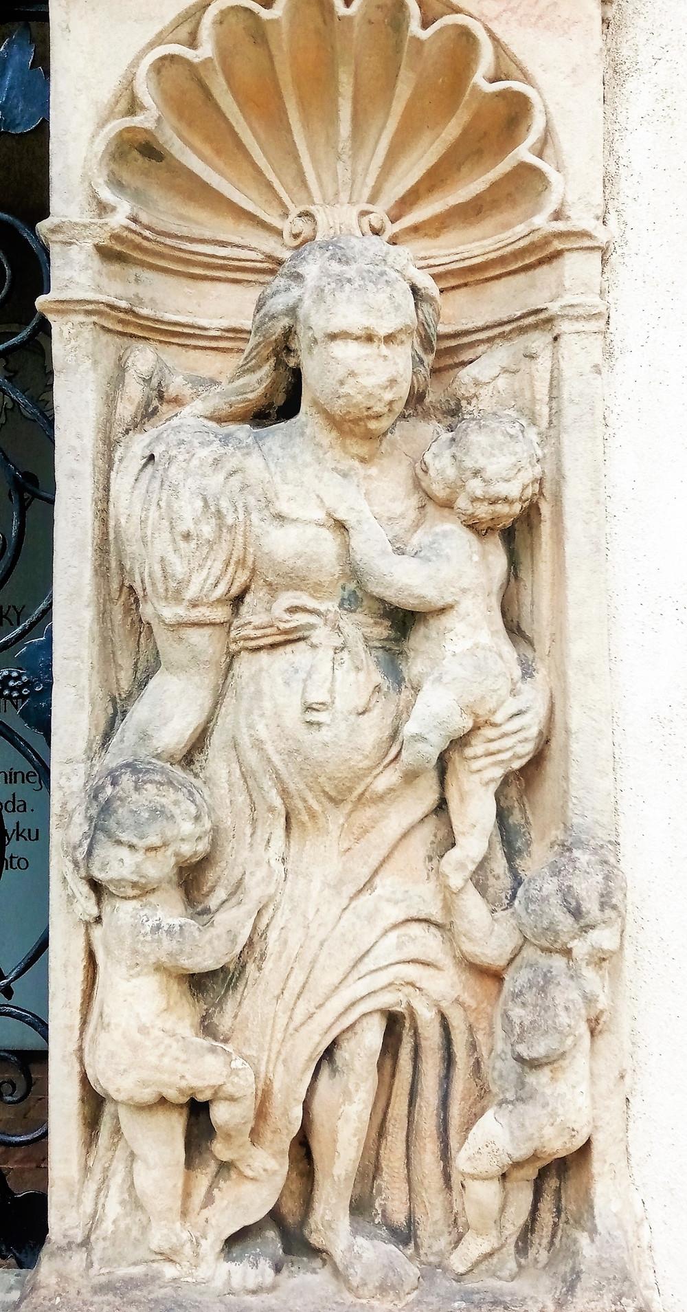 Podoba Charitas, což je alegorie křesťanské lásky, tak jak jí najdeme na hrobce Bukůwků z Bukůwky v Postřelmově