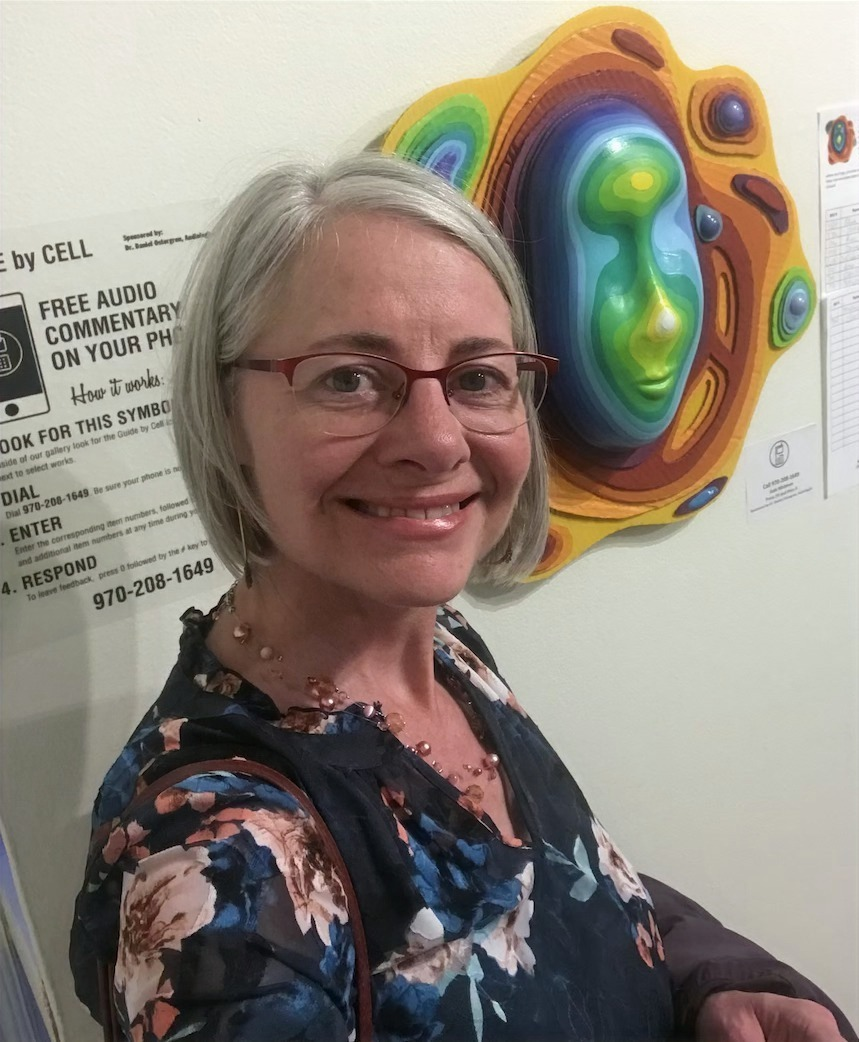 """Gale's selfie with her piece """"Higher Ground"""" at the 2019 Masks Exhibit"""