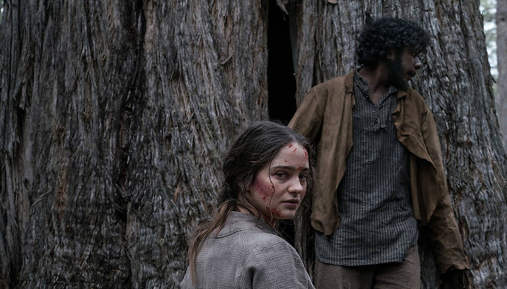 Aisling Franciosi and Baykali Ganambarr in The Nightingale. She has blood on her face as she turns toward the camera and he looks from behind a tree to see if police are nearby