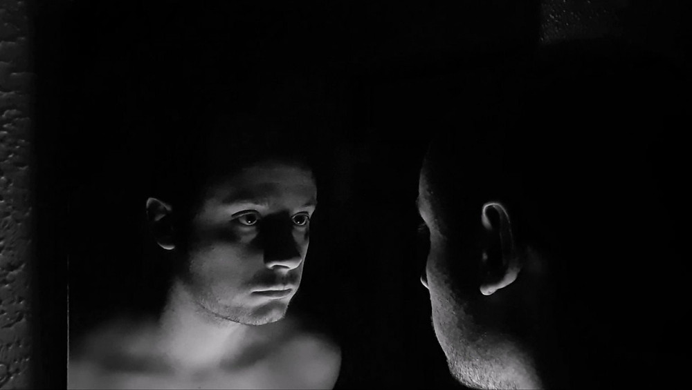 A black and white image of a man staring at his own reflection in the mirror.