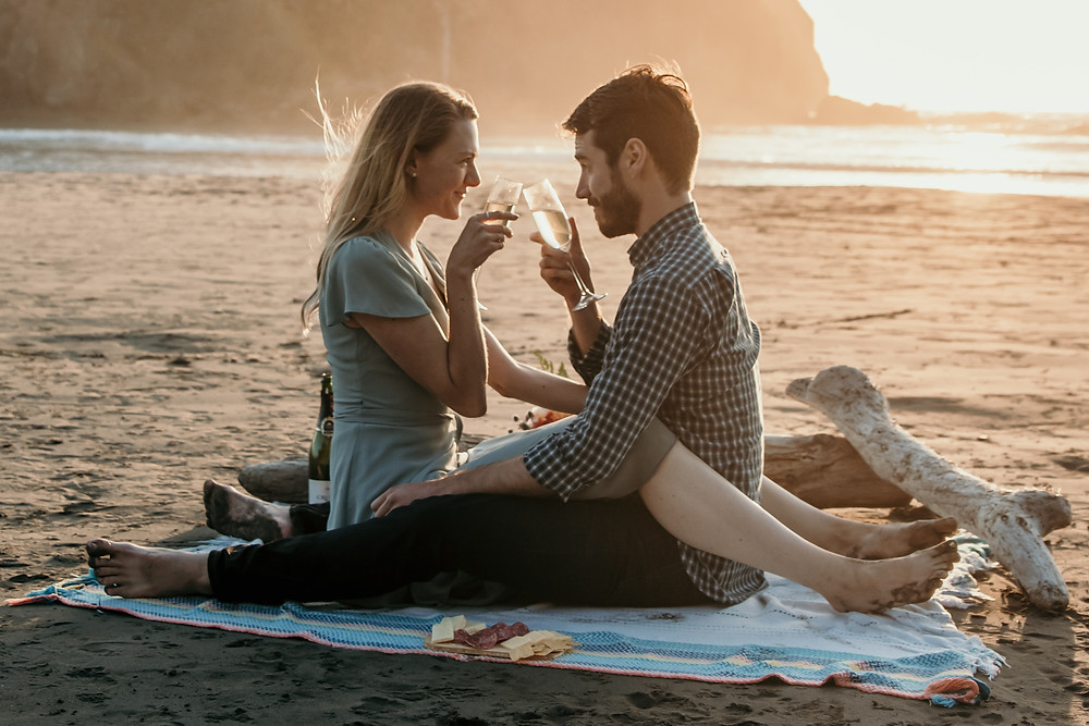 A couple toasts champagne during a picnic on Ruby Beach in Washington