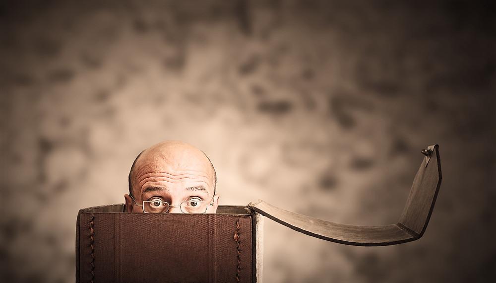 Mann schaut beängstigt aus einer Box