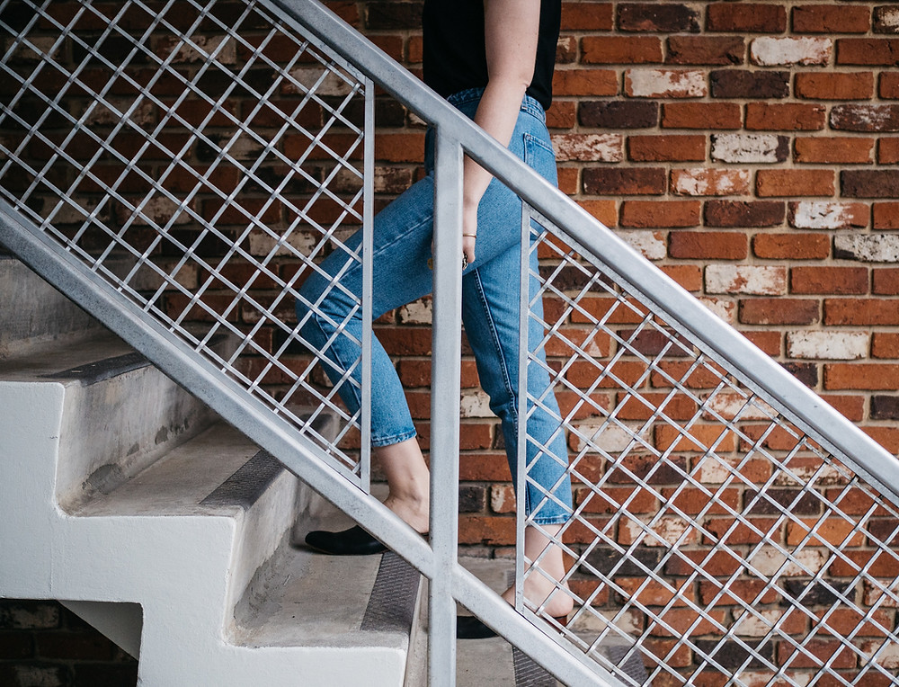 Woman slowly walking up stairs