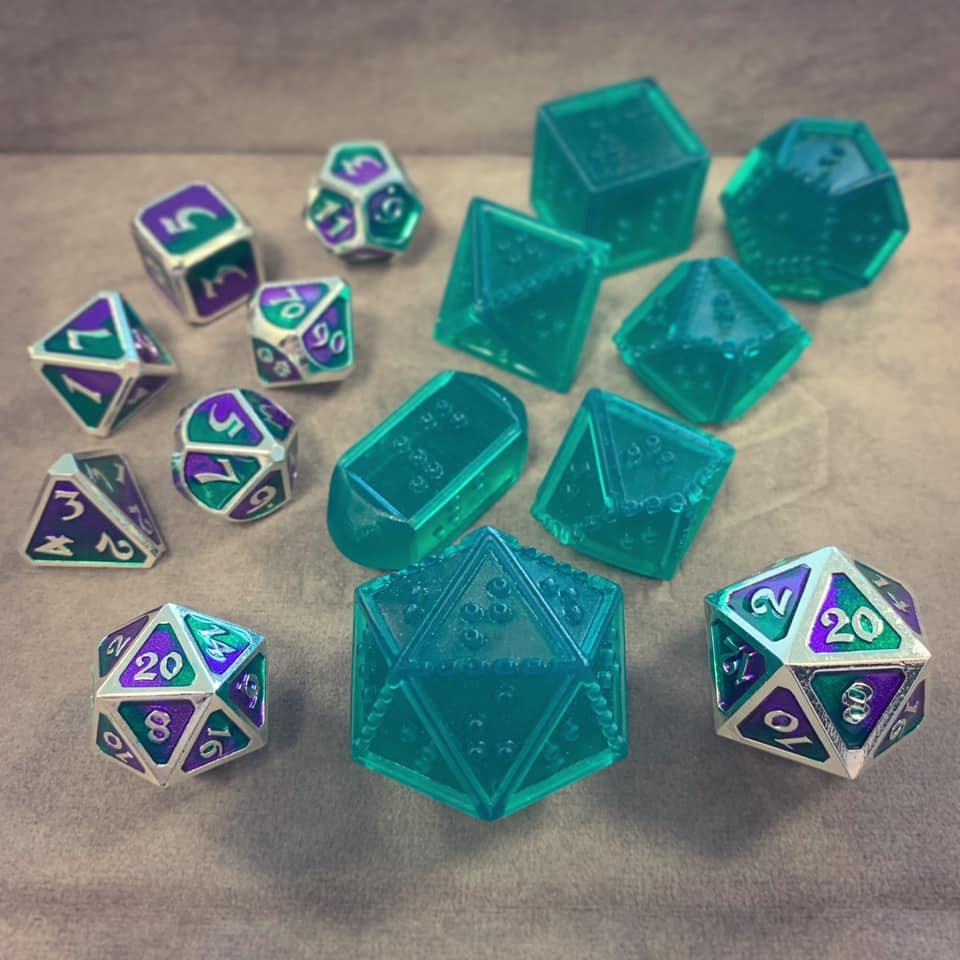 Gray dice tray with green braille dice set, oversized d20 and full set both made of silver metal with purple and green paint on each face.