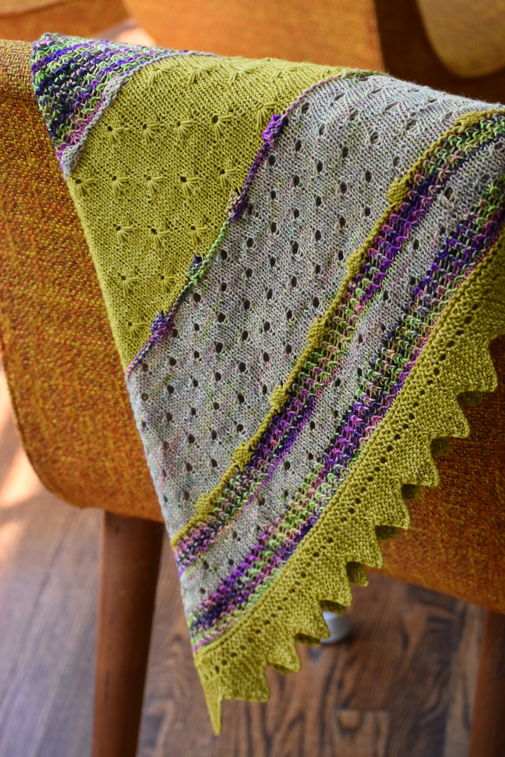 A yellow, purple and oatmeal knit shawl draped on an orange chair