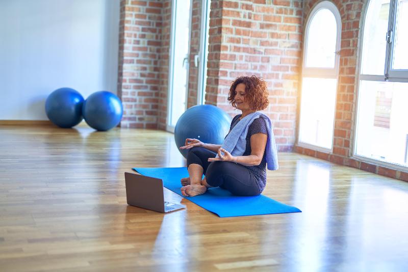 Woman in yoga studio following yoga on laptop