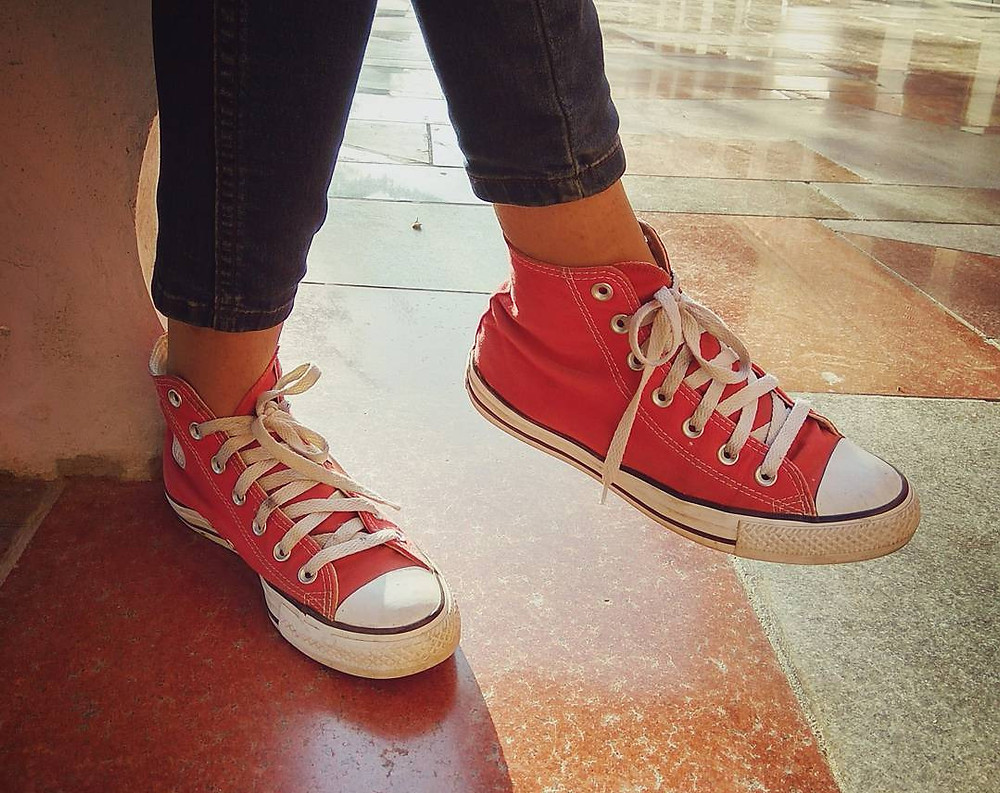 close up photo of a girl wearing Converse shoes