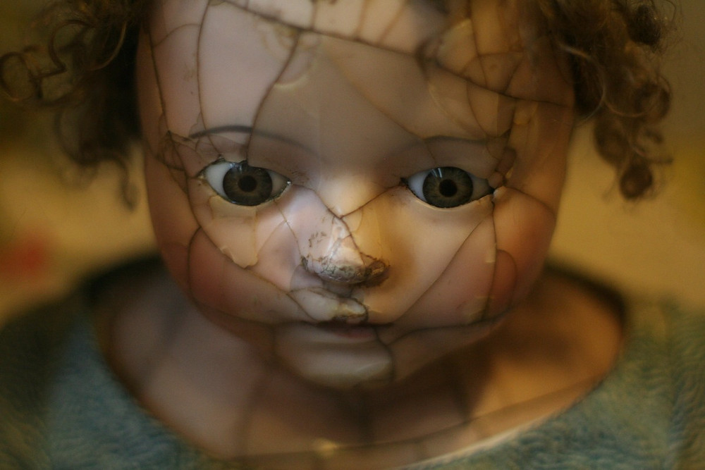 A dolls head with clear fracture lines but pieced together, tear rolling down cheek.