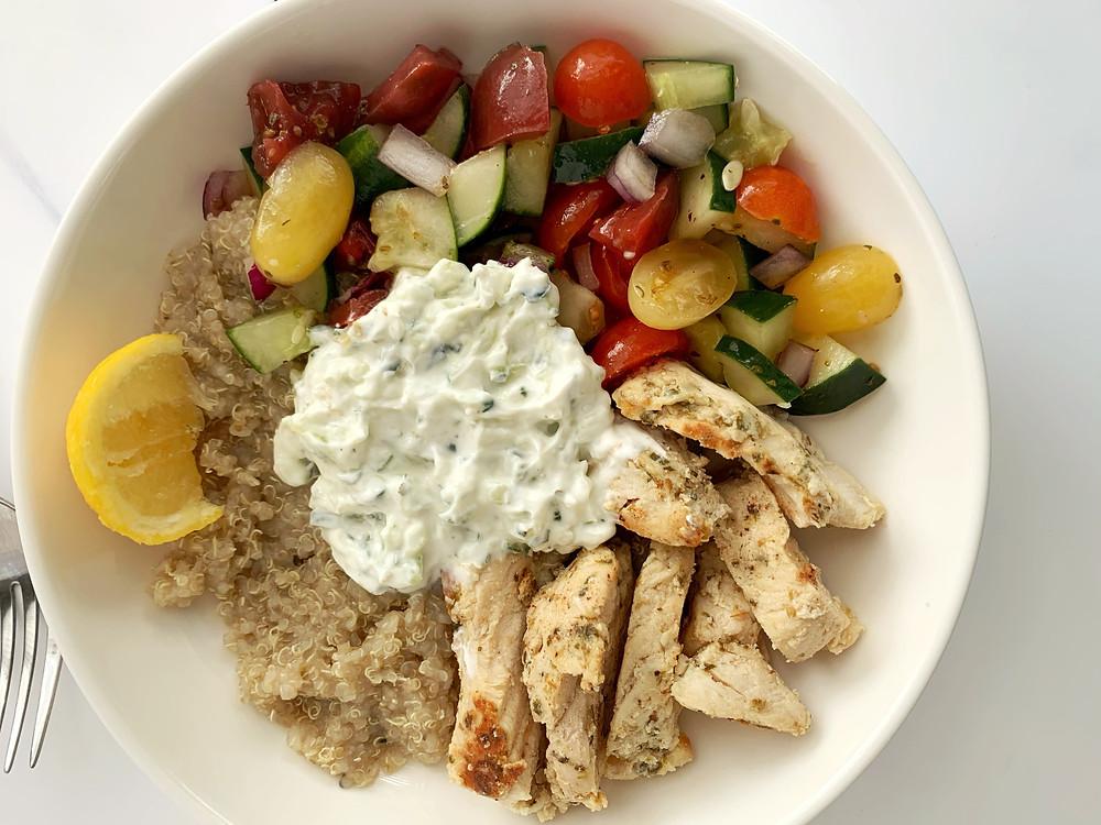 overhead shot of greek chicken quinoa bowls with tzatziki sauce and mixed veggies