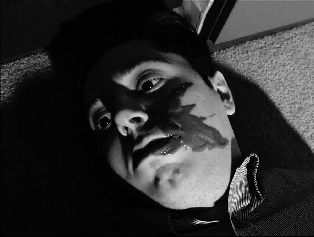 An image from the short film Chocolate City which shows the face of a dead man with chocolate around his mouth