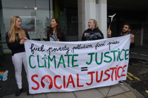"""Four people standing on a street holding a banner saying """"fuel poverty, pollution, food prices, CLIMATE JUSTICE = SOCIAL JUSTICE"""""""