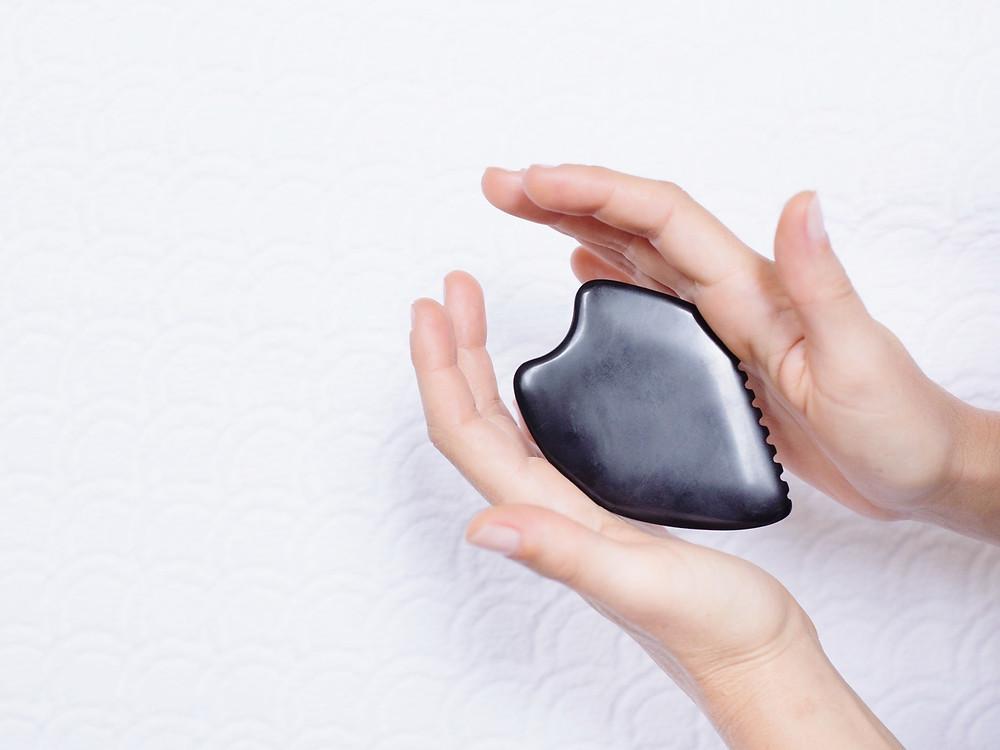 facialist hands holding guasha