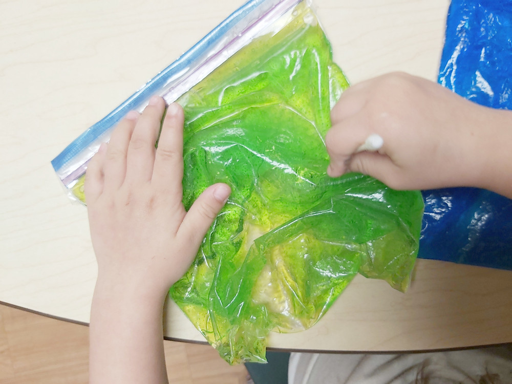 preschooler using sensory writing bag to form letters with q-tip
