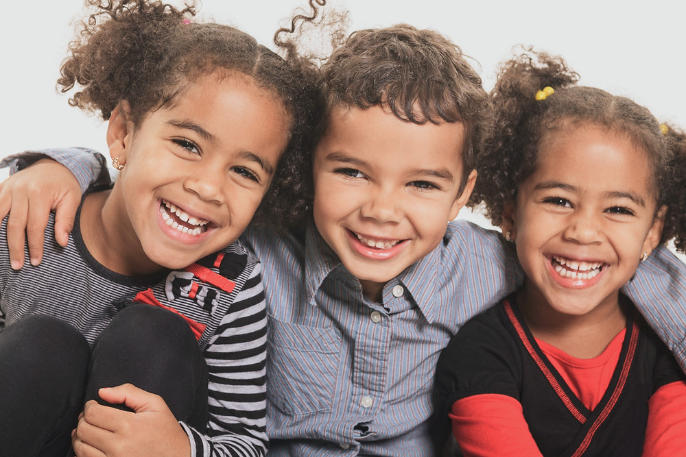 three-black-children-smiling-and-embracing