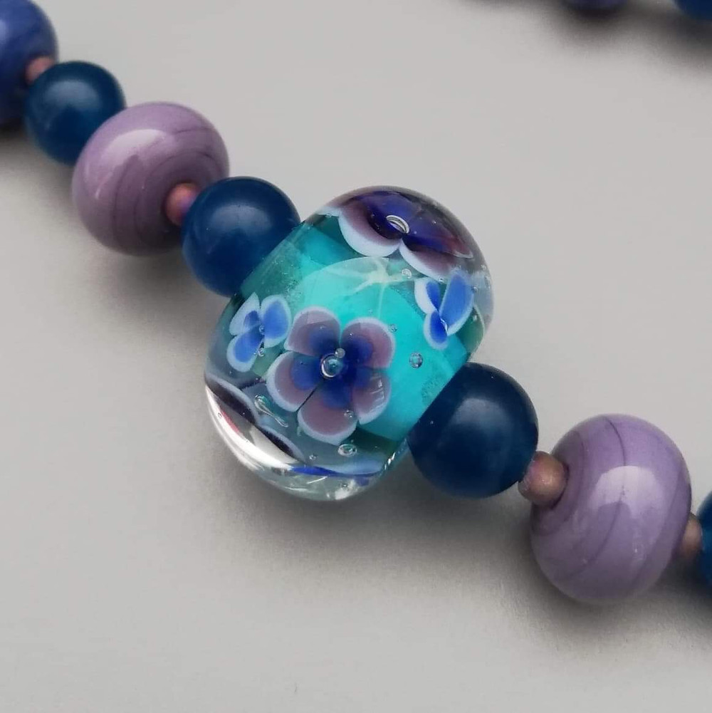 Purple and blue flower bead with green background strung on necklace