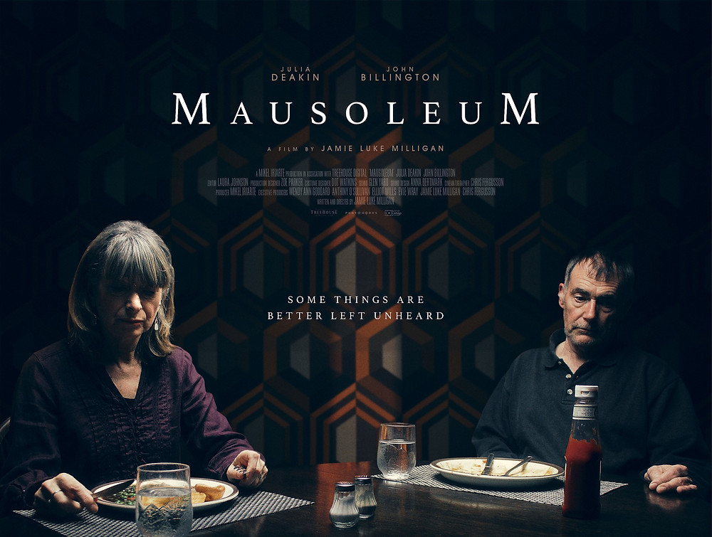 Poster showing a fractured couple sitting at a dining table, eating dinner. The husband seemingly in his own world, whilst the woman has many deep feelings. Bold text at the top of the poster reads 'Mausoleum.'