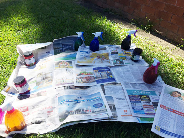 Newspaper weighed down with paint pots and spray bottles.