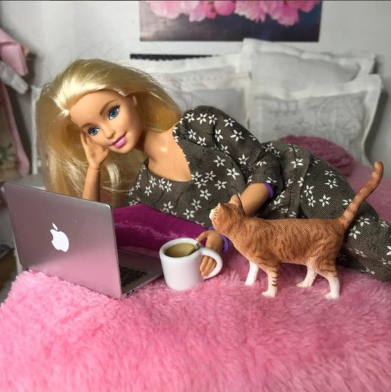barbie doll with cat and drink on computer