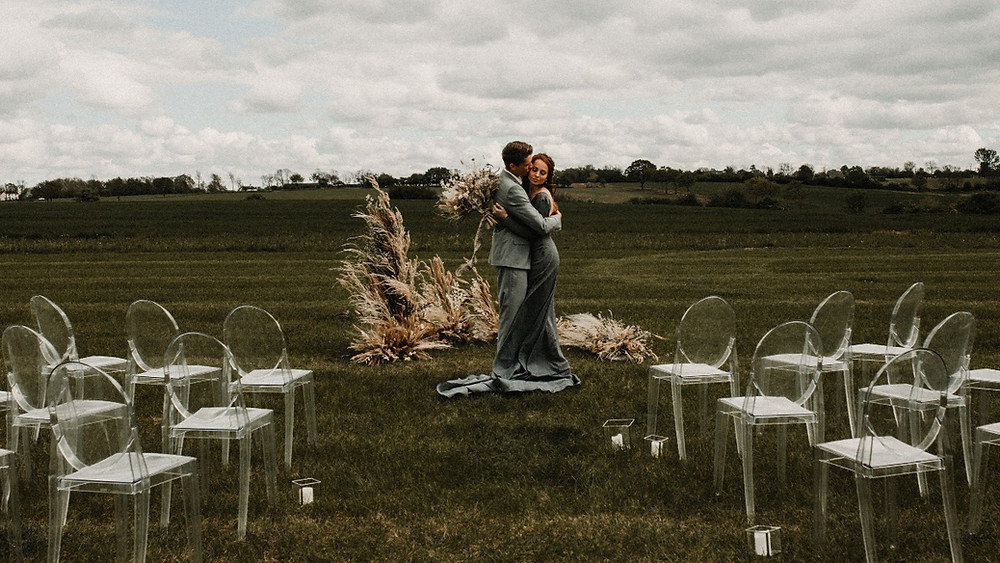 Humanist ceremony couple marry outdoors with ghost chairs and dried flowers