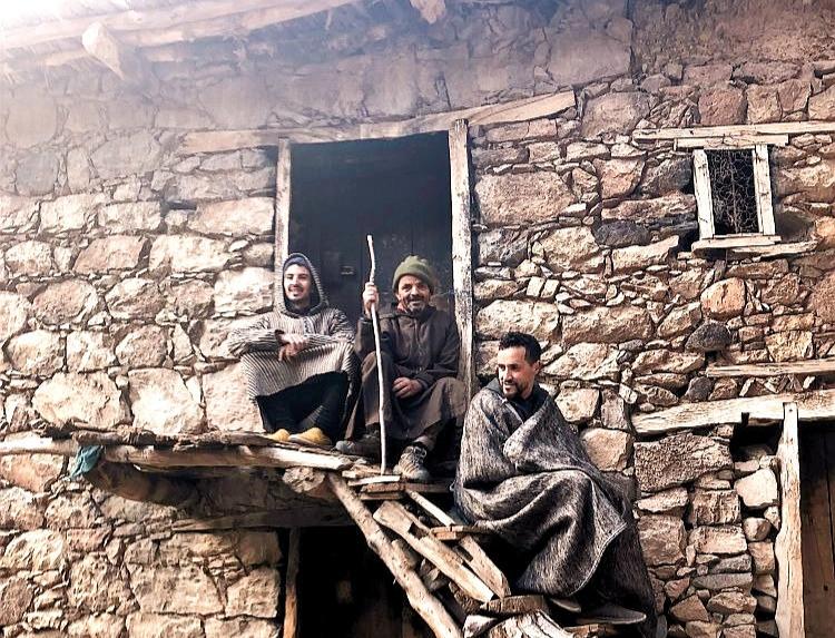 Tři muži v tradiční džilabě na zápraží.