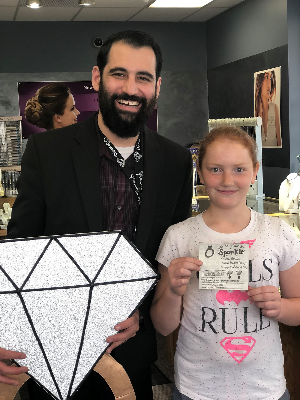 Evan Silbert and Corinne holding Thurber Jewelers advertisement from local newspaper. Thurber Jewelers community contribution. Charitable donations.