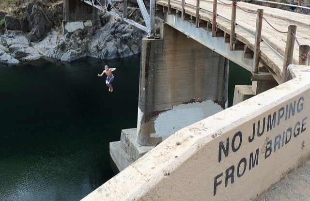 "Despite a sign saying ""No Jumping from Bridge,"" a boy is jumping from the bridge."