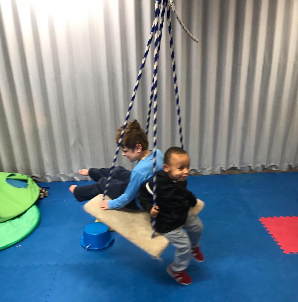preschool students swing together in gross motor room