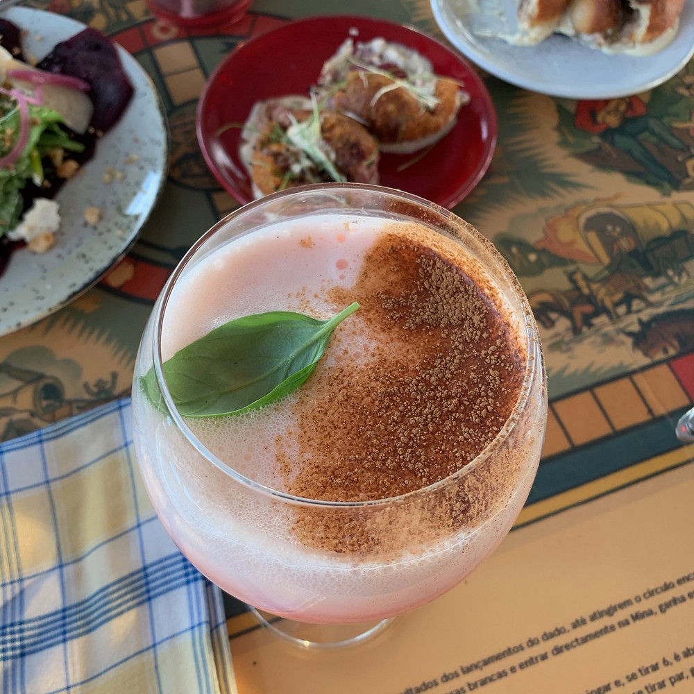 Bubbly light pink drink with cinnamon and a lone basil leaf