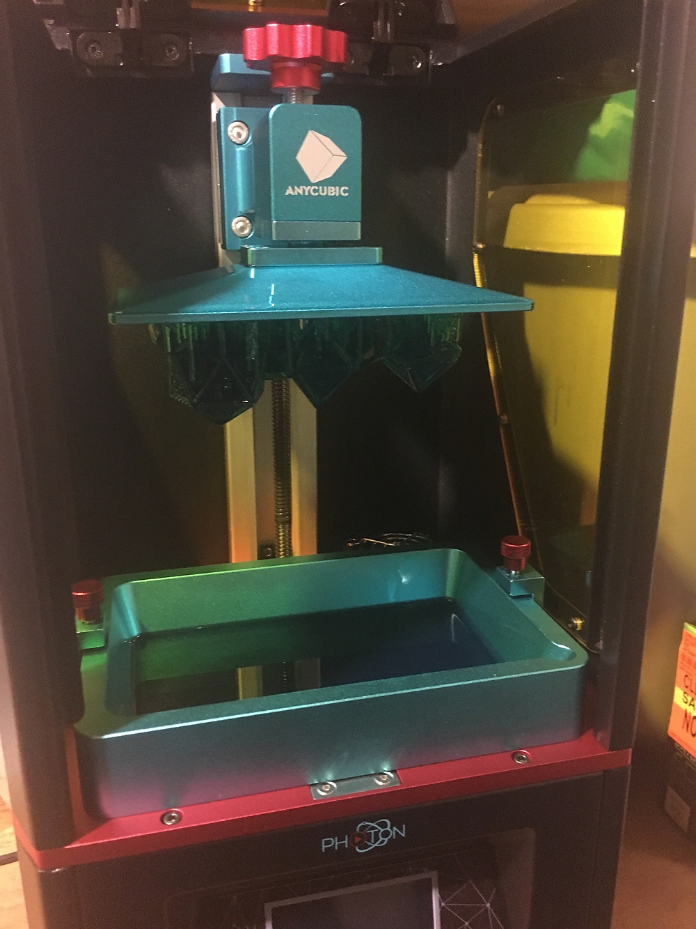 Inside of 3D printer showing build area. There is a flat metal build plate at the top with printed dice hanging off the bottom. Below this is a vat containing liquid resin