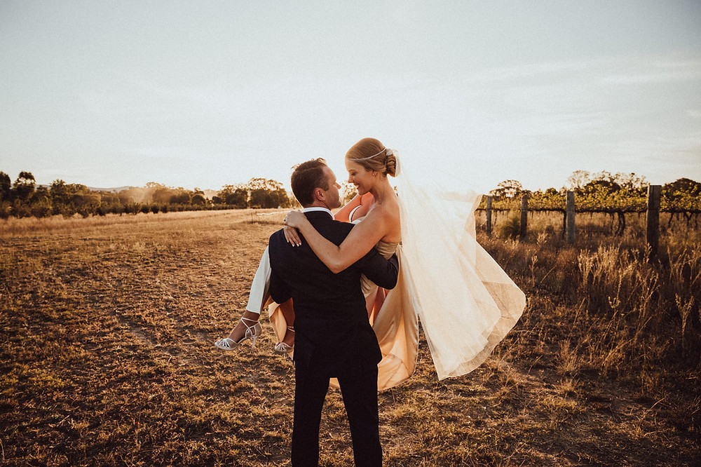 groom carrying his bride through a paddock at sunset at the vinegrove mudgee