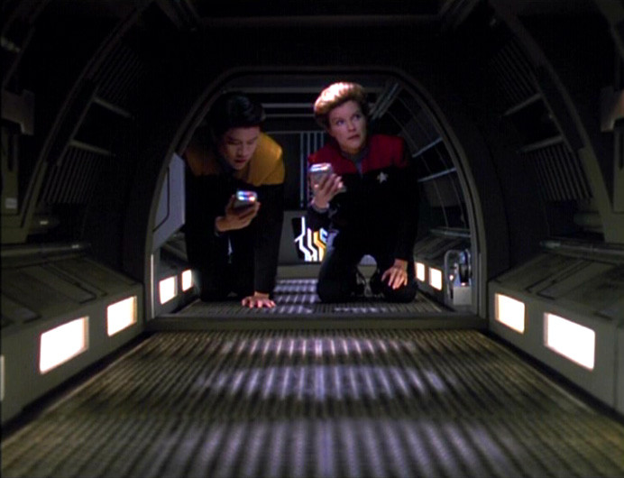 Two crewmembers of the USS Voyager crawling in a GNDN tube