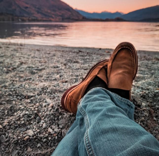 Pessoa sentada com os pés cruzados de frente para um lago, na imagem mostra apenas os pés e a paisagem