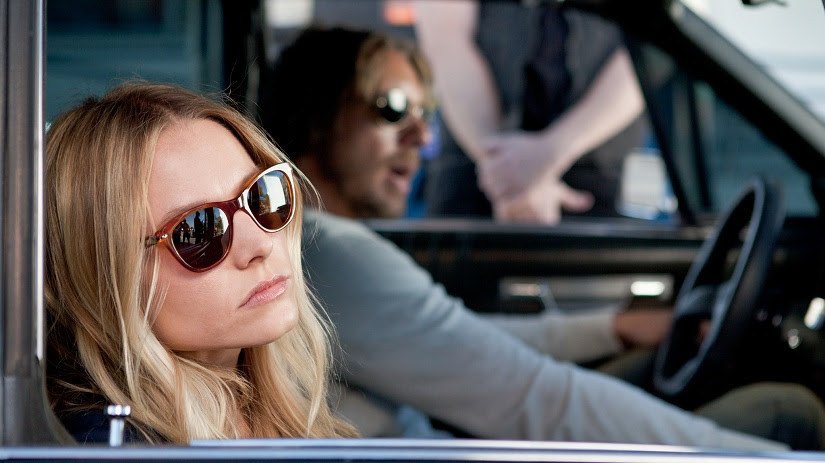 Kristen Bell wearing sunglasses, looking out the car window