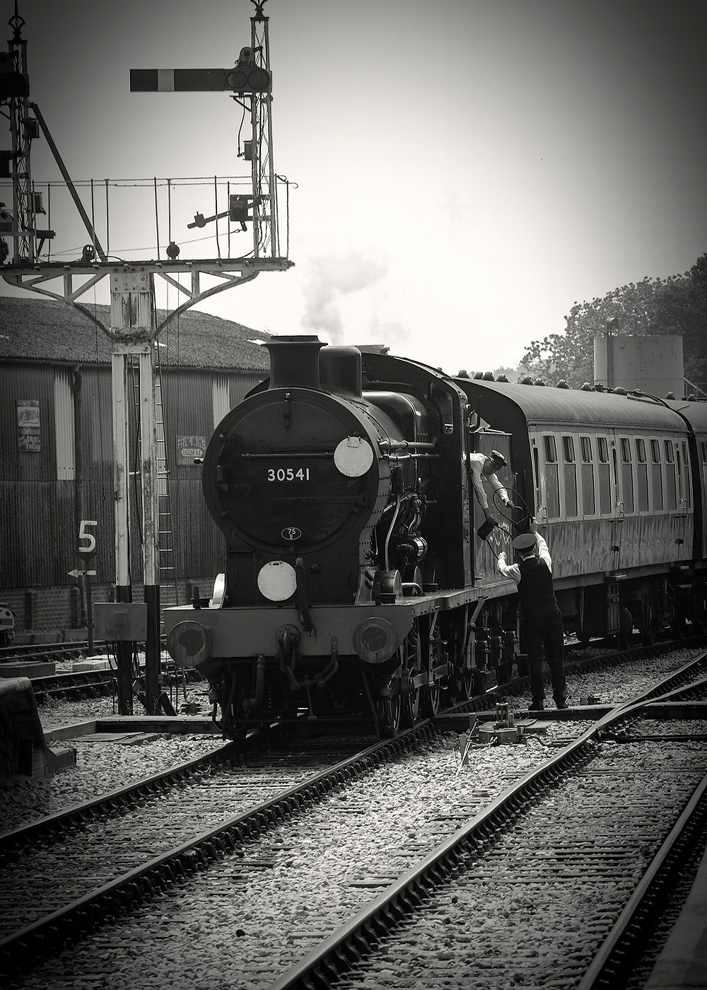Steam train passing a signal with the driver and signal man exchanging an old fashion safety device