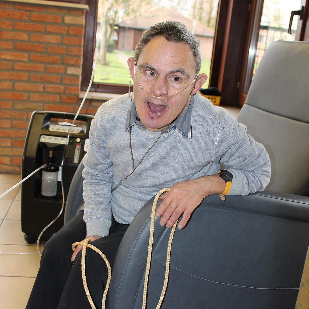 Bewoner Ludo met zuurstoftank naast zijn zetel