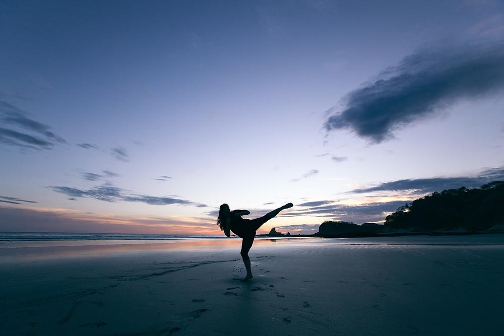 mulher praticando karate na praia