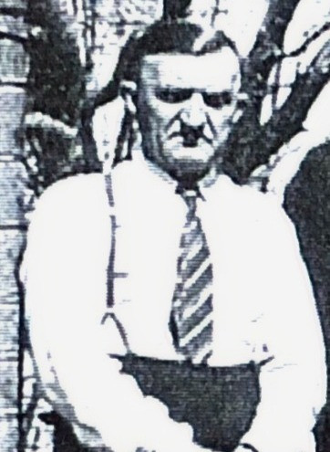 Short man with white shirt, suspenders and a striped tie with his hands folded in front.