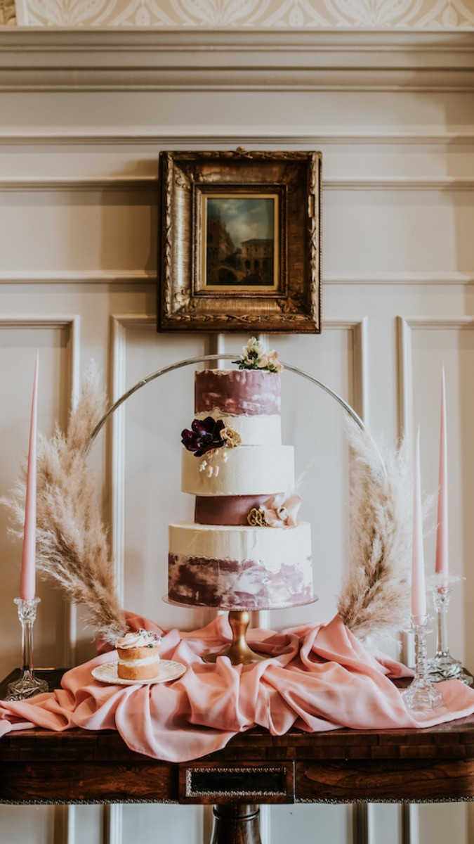 Four tiered wedding cake decorated with fresh flowers and surrounded with a pampas grass cake hoop and Ester and Erik candles in crystal candlesticks at Chippenham Park.