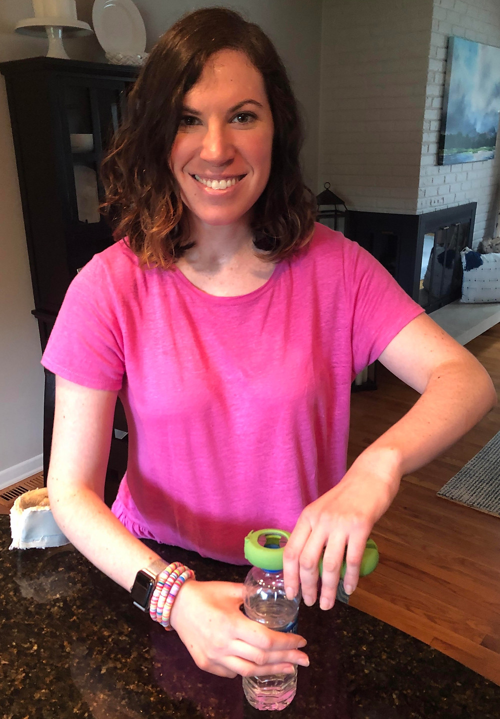This is another image of Molly using er 6 in 1 bottle opener. She is wearing a pink shirt and looking directly at the camera and smiling. She is using her bottle opener to open up a bottle in her kitchen.