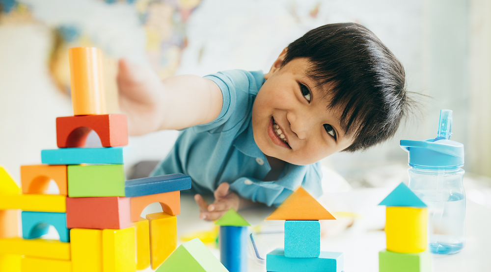 A preschooler playing with wooden blocks - an educational toy.