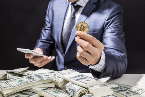 Wealthy Banker Sitting In Front Of Dollar Bills And Holding His Bitcoin Investment In His Hand