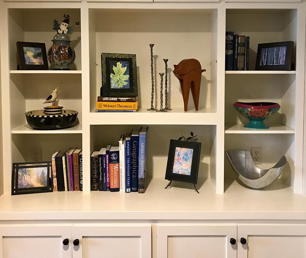 Bookshelves with Kate Moynihan mini framed paintings