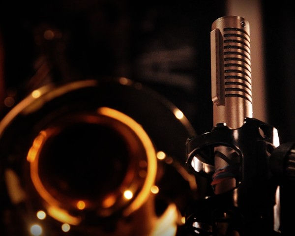 A shiny trombone bell facing a Royer ribbon microphone