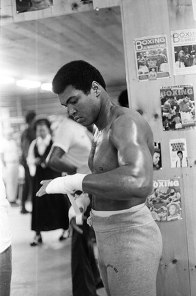 Ali at his camp, preparing for a ring workout with a bevy of onlookers, 1974