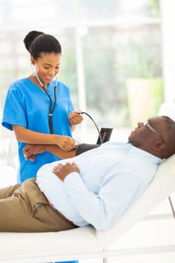 doctor checking senior patient's blood pressure